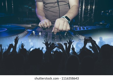 Mixing DJ at a party in a double exposure with a partying crowd.