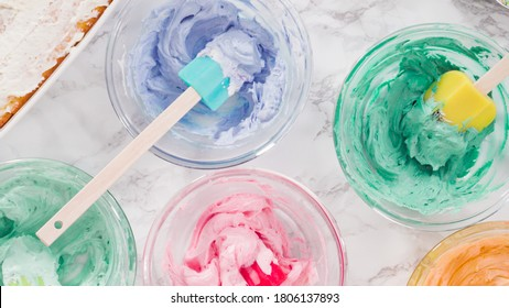 Mixing food coloring into Italian buttercream frosting.