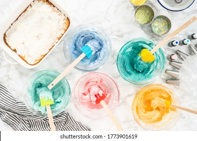 Mixing food coloring with Italian buttercream frosting.