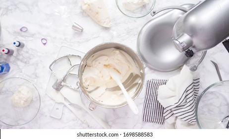 Mixing ingredients in standing kitchen mixer to make buttercream frosting.