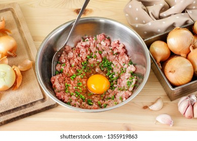 Mixing meat and eggs to prepare the meatballs.