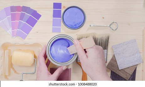 Mixing new purple  paint with wooden paint stick.