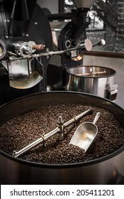 Mixing roasted coffee in roaster cooling container with a scoop