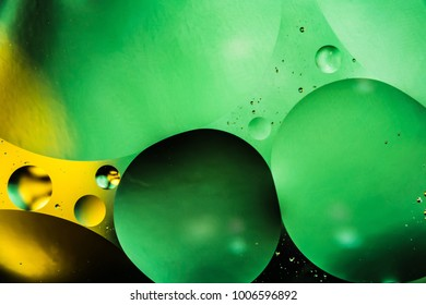 mixing water and oil, beautiful color abstract background based on green and yellow circles and ovals, macro abstraction