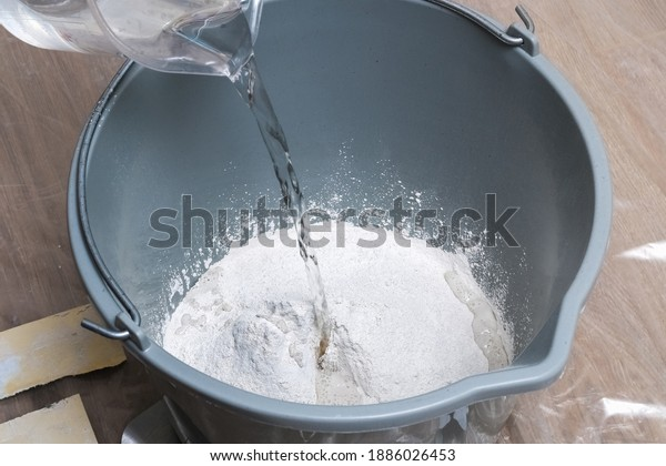 Mixing white plaster in a bucket with a stirrer. Close-up.