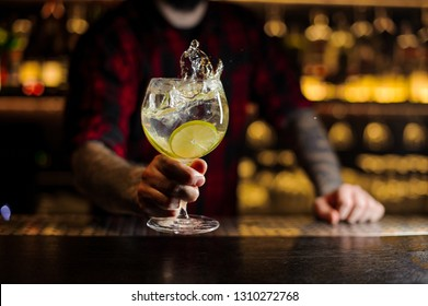 Mixologist holding a cocktail glass with fresh sour and sweet citrus drink with slices of lime