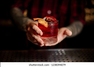 Mixologist holding a glass of strong fresh whiskey cocktail decorated with orange peel on the bar