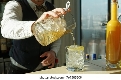 Mixologist is making cocktail on rocks, straining from mixing glass