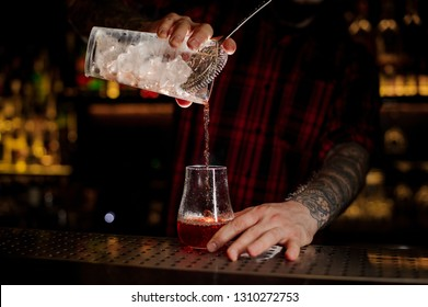Mixologist pouring fresh and tasty bittersweet red cocktail into an empty cocktail glass on bar