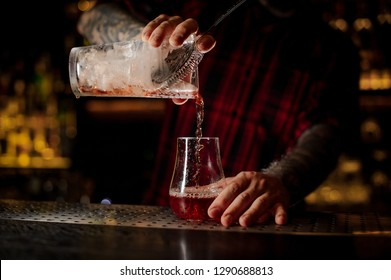 Mixologist pouring fresh and tasty cool bittersweet red cocktail into an empty cocktail glass on bar