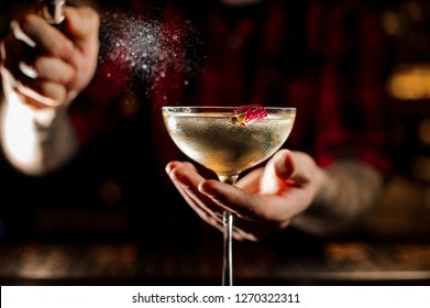 Mixologist sprinkling bitter on the elegant cocktail glass decorated with a little rose bud against the lights