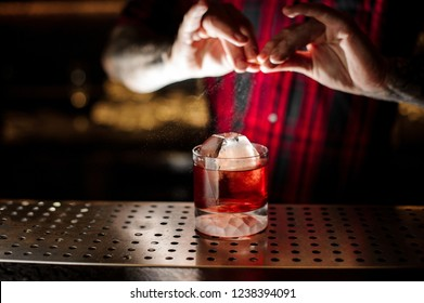 Mixologist sprinkling orange peel juice into a cocktail glass filled with strong dark drink with whiskey