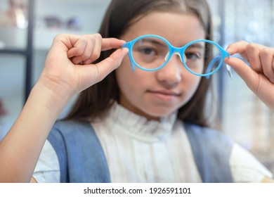 Mix-race girl trying new glasses in optician store, looking through eyes glasses to camera, selective focus