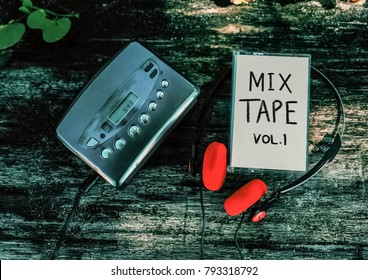 Mixtape and cassette player with red vintage earphones on wood background