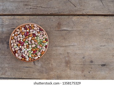 Mixture of beans varieties,azuki and green lentils in a bowl on a weathered wooden plank. Food background for copy space