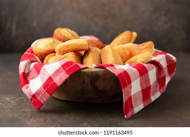 Mixture of Homemade Cornbread Sticks, Muffins, and Slices in a Wooden Bowl Lined with Red and White Checked Napkin; Dark Background