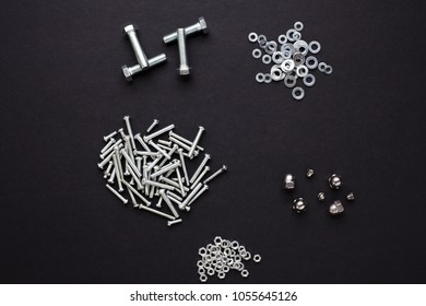 A mixture of nuts, bolts and washers on black surface. Shot top down