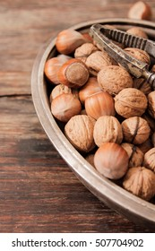 mixture of nuts on a metal plate with orehokolom on a wooden background