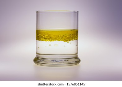 Mixture of olive oil and water in glass, isolated on white
