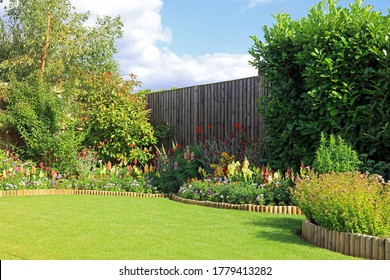 A Mixture Of Pretty Flowers And Bushes In A Well Maintained English Garden.