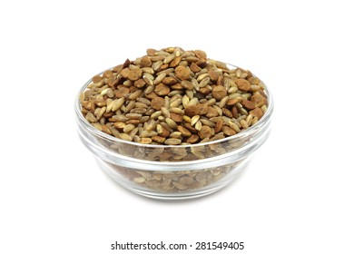 a mixture of raw grain cereals in a glass cup on a white background