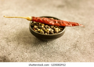 A mixture of red, black and white peppers on a concrete background