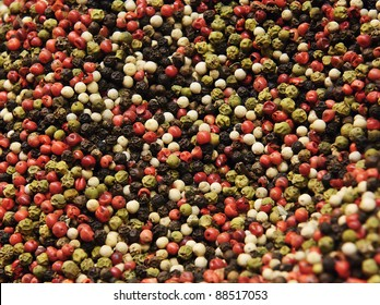 A mixture of red, green, white and black pepper corns.