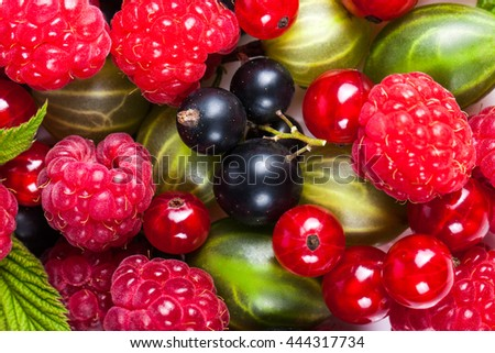 A mixture of ripe juicy fruits and berries on a white background. Raspberries, currants, gooseberries close-up. Beautiful fruit background