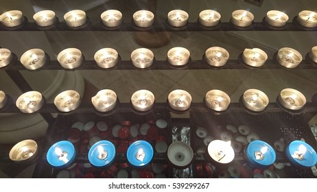 Mixture of white and blue candles in a big row at the back of a church