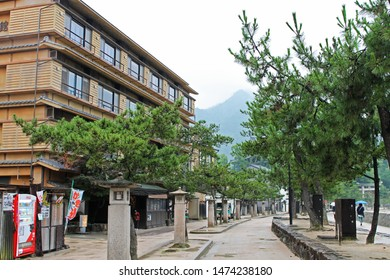 Miyajima, Hiroshima, Japan, - 07.05.2018: A line of pine trees and lanterns lead the way from the Miyajima ferry to the Itsukushima Floating Gate, past an apartment building on a rainy day.