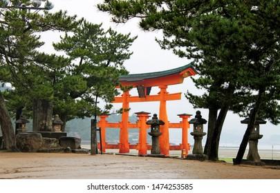 Miyajima, Hiroshima, Japan, - 07.05.2018: Looking through lanterns and pines trees towards the famous Itsukushima Floating Torii gate on Miyajima Island near Hiroshima, Japan on a misty and rainy day.