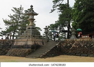 Miyajima, Hiroshima, Japan, - 07.05.2018: Visitors carrying umbrellas walk down the steps leading to the beach near the Itsukushima Floating Gate on Miyajima Island, past lanterns and pines trees.