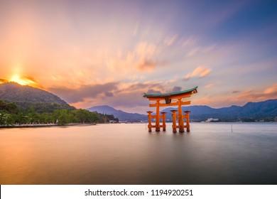 """Miyajima, Hiroshima, Japan at Itsukushima Shrine's floating gate after sunset. (torii gate reads """"Itsukushima Shrine"""")"""