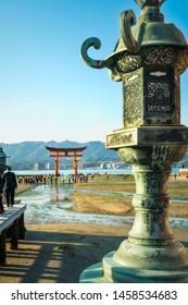 Miyajima Island, Hiroshima Bay, Japan - November 7, 2018: Close-up view of a decorated bronze lantern with the famous Torii Gate in soft focus in the background - Itsukushima Shrine, Miyajima, Japan.