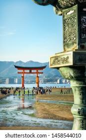 Miyajima Island, Hiroshima Bay, Japan -November 7, 2018: The famous Torii Gate with a decorated bronze lantern closeup in soft focus - Itsukushima Shrine, Miyajima, Japan.