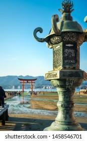 Miyajima Island, Hiroshima Bay, Japan -November 7, 2018: Close-up of a decorated bronze lantern with the famous Torii Gate in soft focus in the background - Itsukushima Shrine, Miyajima, Japan.