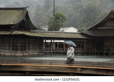Miyajima Island, Hiroshima, Japan - November 14, 2015: A kid in tradational kimono is walking with umbrealla under rain on Miyajima Island