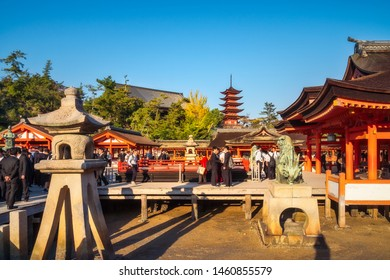 Miyajima Island, Hiroshima, Japan -November 7, 2018: People visiting centuries-old Itsukushima Shrine - Hira-butai, the open-air stage -next to the Main Shrine with the Japanese Pagoda in background.