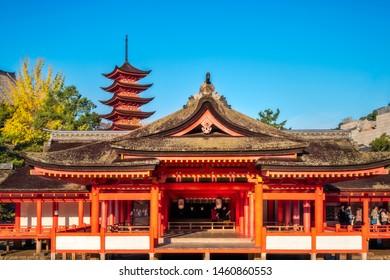 Miyajima Island, Hiroshima, Japan -November 7, 2018: Itsukushima Shrine main shrine and the Purification Hall with the pagoda tower in the background at the sacred island of Miyajima in japan.