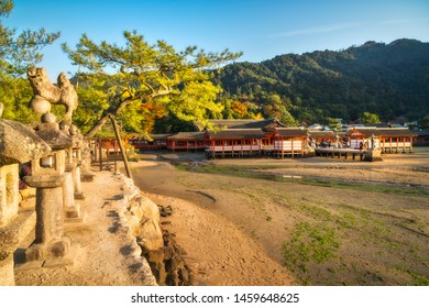 Miyajima Island, Japan-November 7, 2018: Itsukushima Shinto shrine with stone lanterns in the foreground. The Shinden architectural style complex is built on stilts by the sea, so the tide can go in.