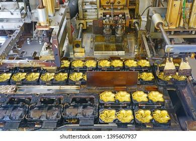 MIYAJIMA, JAPAN -26 FEB 2019- View of a machine making Momiji Manju maple bun cakes, a food specialty in Miyajima, Japan.