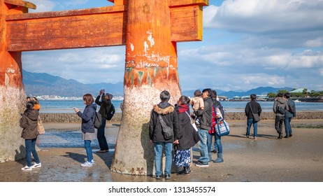 MIYAJIMA, JAPAN - DECEMBER 10, 2016: Landscape photo of tourists seeing the famous torii gate of Itsukushima Shrine up-close during low tide which appears to float on water at high tide.