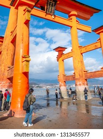 MIYAJIMA, JAPAN - DECEMBER 10, 2016: Vertical photo of tourists seeing the famous torii gate of Itsukushima Shrine up-close during low tide which appears to float on water at high tide.