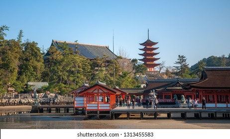 MIYAJIMA, JAPAN - DECEMBER 10, 2016: Tourists walking around at the Itsukushima Shrine, with its multiple buildings, which are connected by boardwalks and supported by pillars.