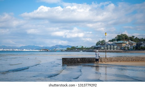 MIYAJIMA, JAPAN - DECEMBER 10, 2016: A Japanese woman taking photos of the view with the West JR Miyajima Ferry Terminal jetty and Hiroshima University of Economics Seminar House in the background.
