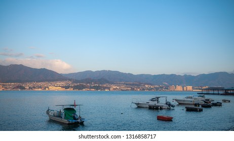 MIYAJIMA, JAPAN - DECEMBER 10, 2016: Landscape photo of the beautiful view that can be seen from the coast of Miyajima Island with several small boats and the West JR Miyajima Ferry Terminal jetty.
