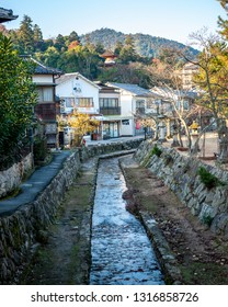 MIYAJIMA, JAPAN - DECEMBER 10, 2016: Vertical photo of a river stream and traditional wooden townhouses, with the top of Tahoto Pagoda visible in the background, located in the famous Miyajima Island.