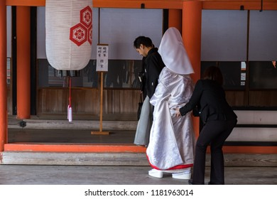 MIYAJIMA, JAPAN - FEB 03, 2018: Japanese bride getting married in Itsukushima shrine wearing white and red traditional clothes