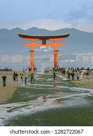 Miyajima, Japan - NovemberR 20, 2016: The great O-Torii of Itsukushima Shrine.  Tourists walk around the famous floating torii gate of the Itsukushima Shrine on Miyajima at low tide in Miyajima, Japan