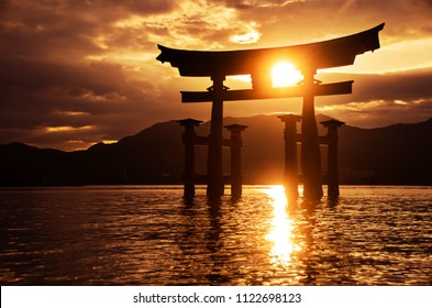 Miyajima Torii gate in the sea with the sun shining through the structure over the mountains during a golden sunset.